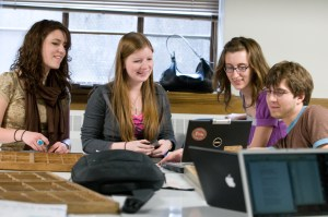 Students work together in a group around laptop computers