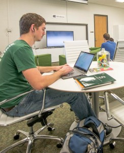 An MSU student uses a laptop in a study room on campus.
