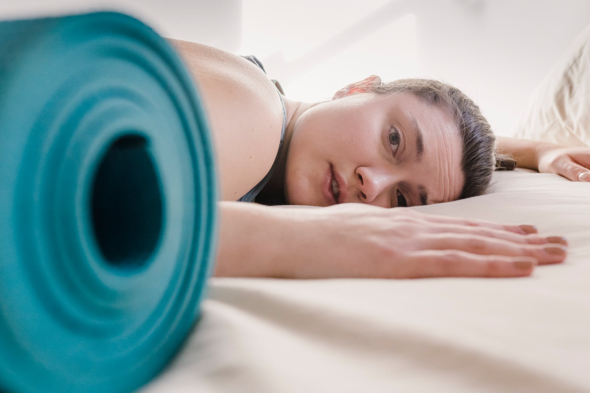 tired woman lying on bed during workout