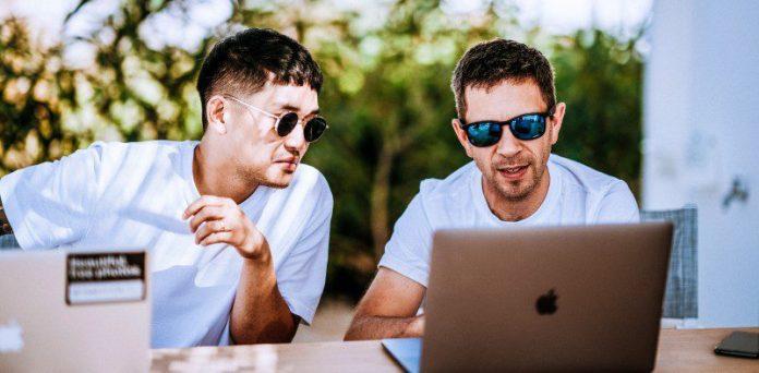 Two Men working outside on laptops dev coding programming saas cloud platform on prem Mirantis solution