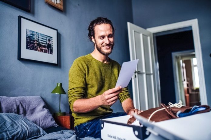 Outfittery Press Material Photo Man Sitting On Bed Checking Parcel Clothing Fashion Startup FashionTech Review Test