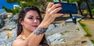how_to_download_from_instagram_igtv_photos_videos_woman_in_black_sleeveless_shirt_with_tattoo_on_her_left_arm_selfie