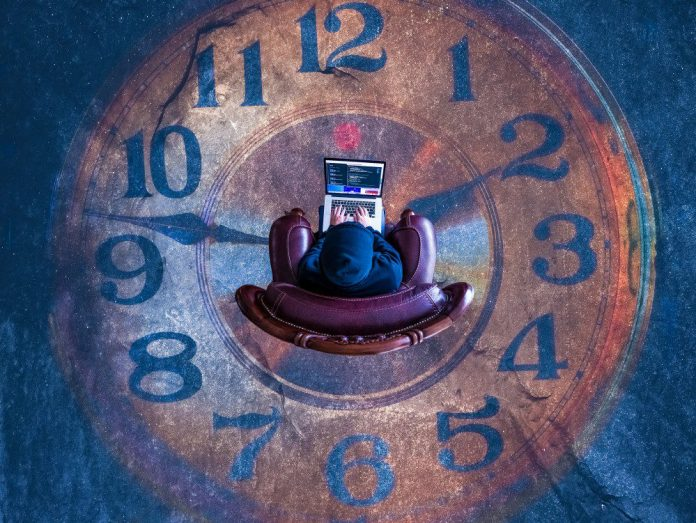 Man Sitting Time Running Past Clock Ground Working Laptop Chair Above Theseus Inc