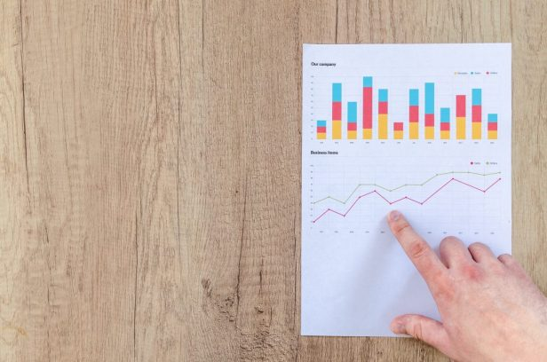 Man showing business graph on wood table