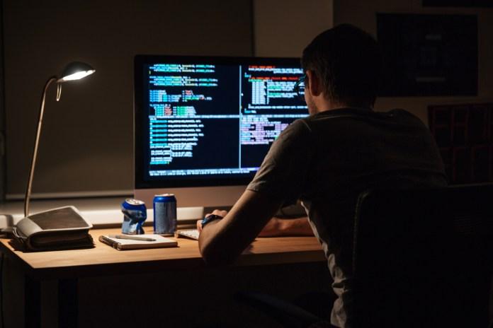 Man coding on computer at night.