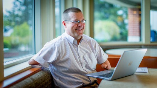 CEO of Our Ability John Robinson sitting, smiling and in front of his laptop