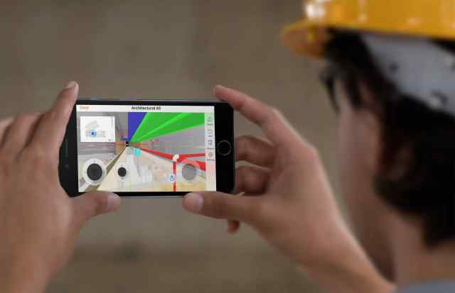 black iphone in landscape position held by a construction worker with a yellow hat a12584