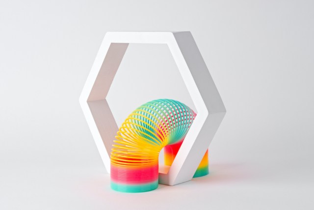 Flexible Multi Colored Coil Crossing Hexagon Frame on White Background.