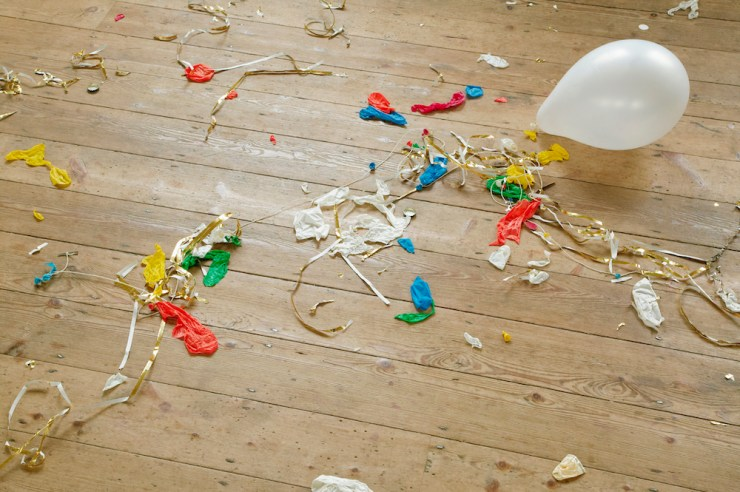 Burst balloons and party streamers on wooden floor