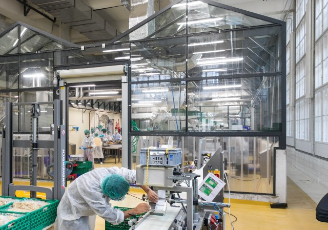 A large laboratory environment with clear walls. A person works at machinery in the foreground.
