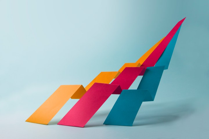 Abstract minimalist conceptual multiple coloured zig zag strip joined as one moving upwards on blue background.