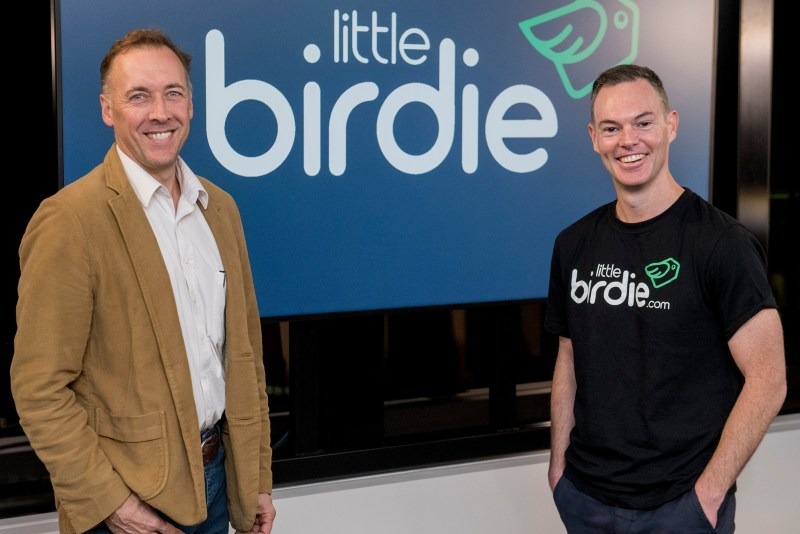 A photo of (left) Commonwealth Bank group executive Angus Sullivanand (right) Jon Beros, co-founder and CEO of Little Birdie, standing in front of Little Birdie's logo