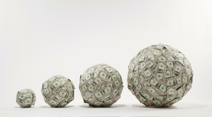 4 progressively larger balls of US $1 bills, studio shot
