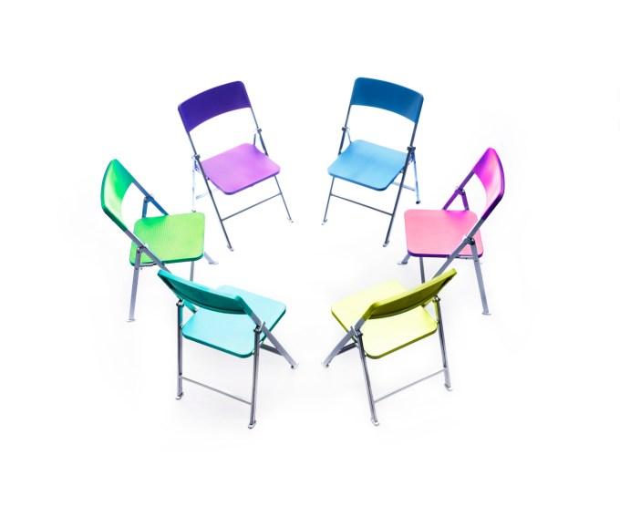 Círculo de sillas de diferentes colores.