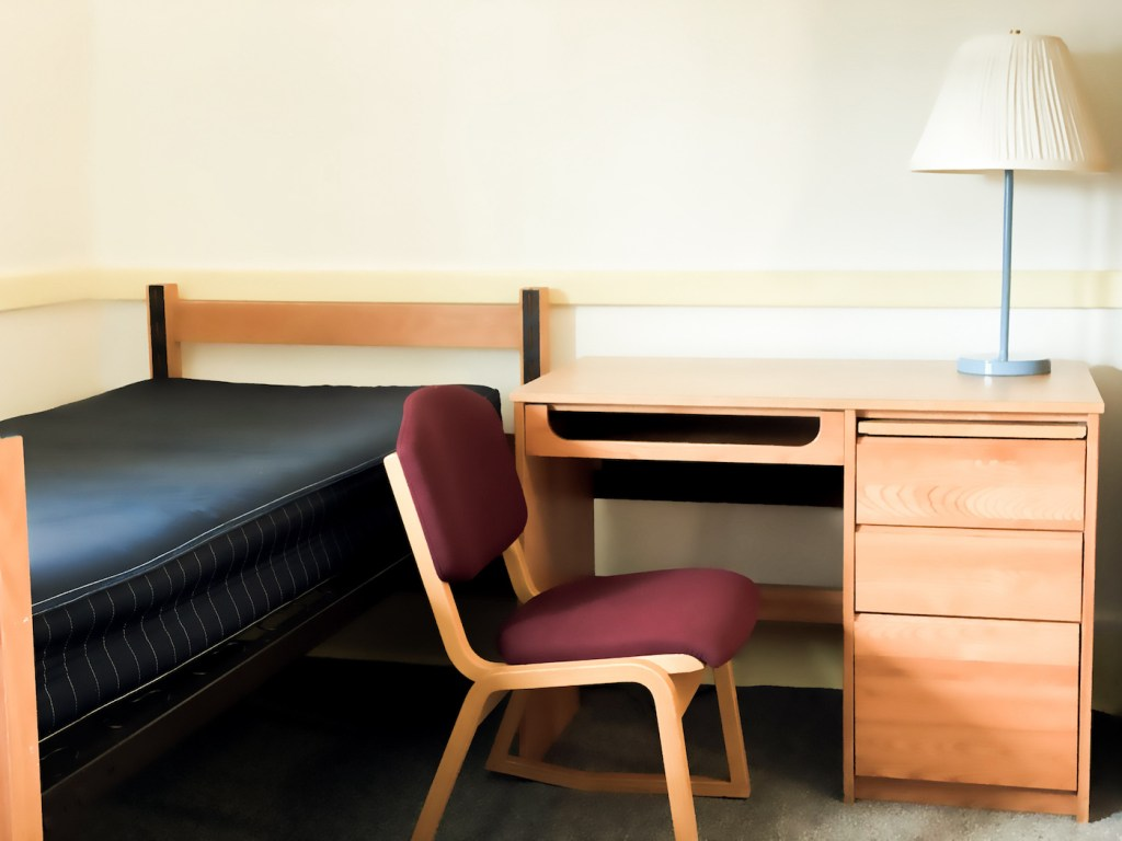 student dormitory room with bed, desk & chair