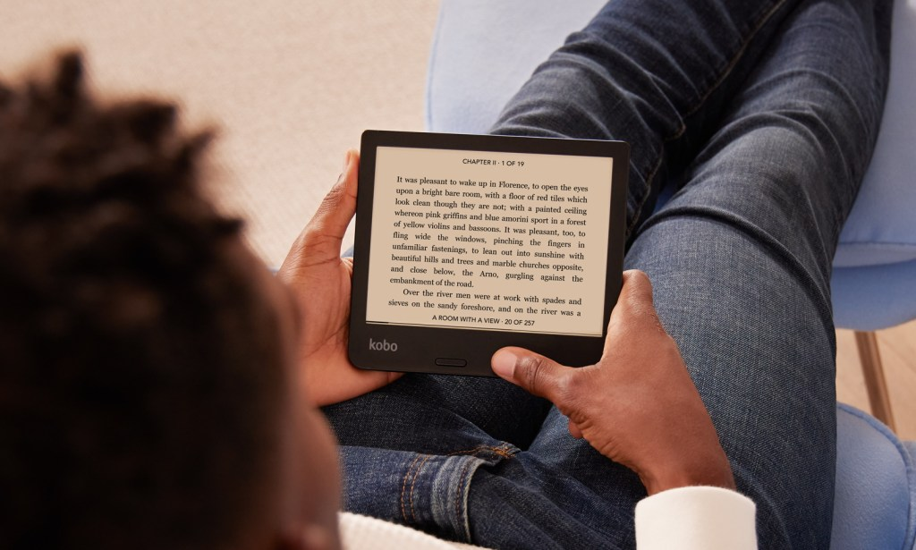 A man sitting on a couch reading on a Libra e-reader.