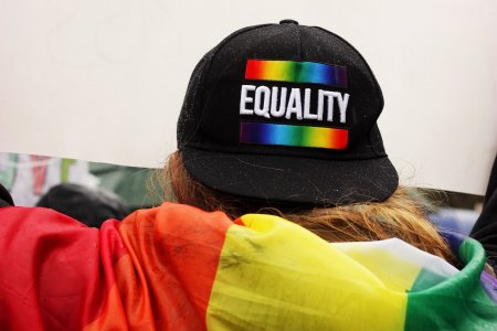 """Person wearing hat saying """"equality"""" and with rainbow flag"""