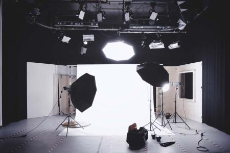 Photo studio with lighting and white backdrop. Photo by Alexander Dummer on Unsplash