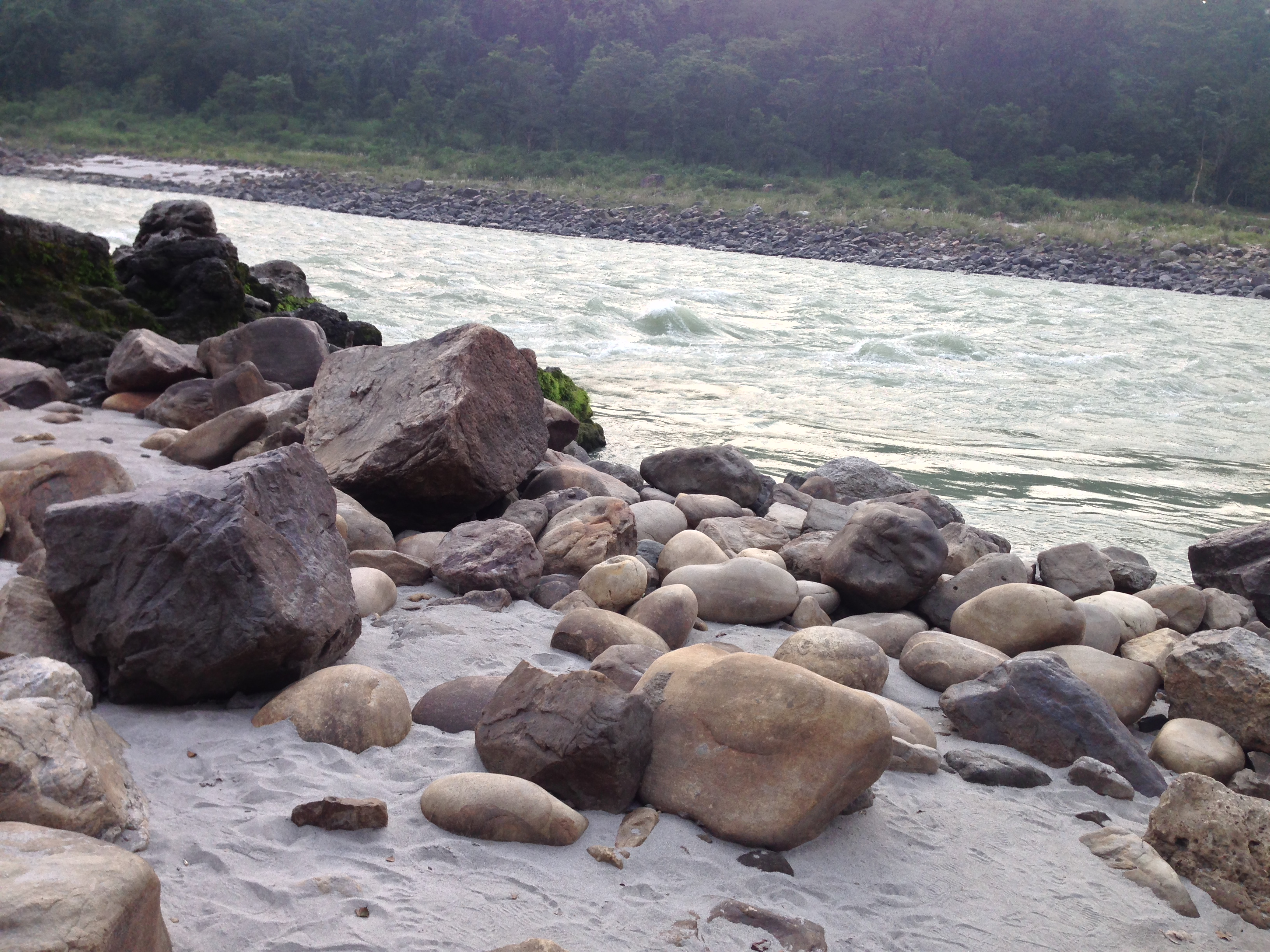 A raging river, ideal for rafting with rocks of different shapes. Both the near and far shore are visible. The river is in the background. The rocks on the near shore are one of the most prominant feature's of this image.