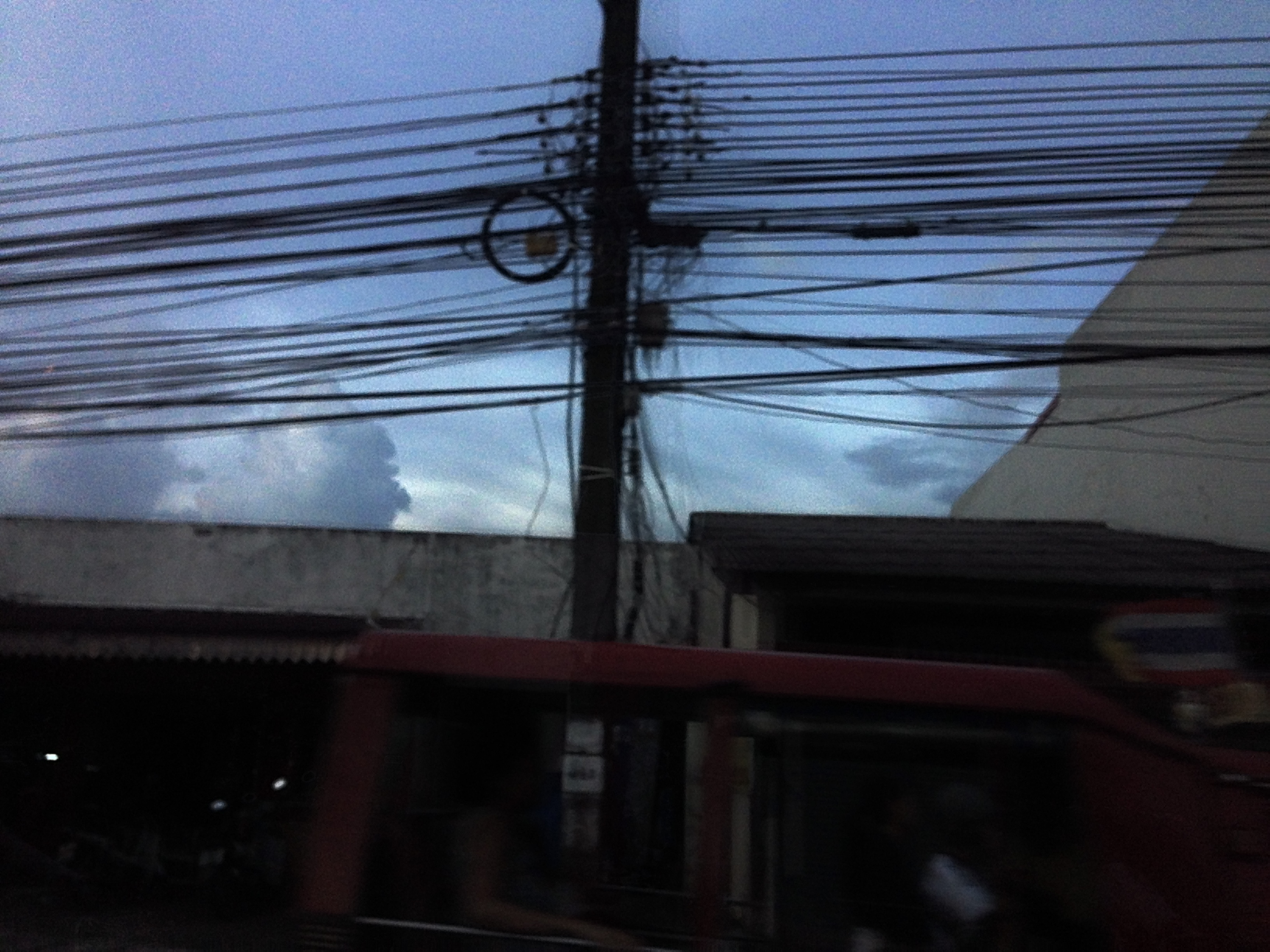 Electric pole with wires running across the middle of the photo. Sky in the background and a low building in