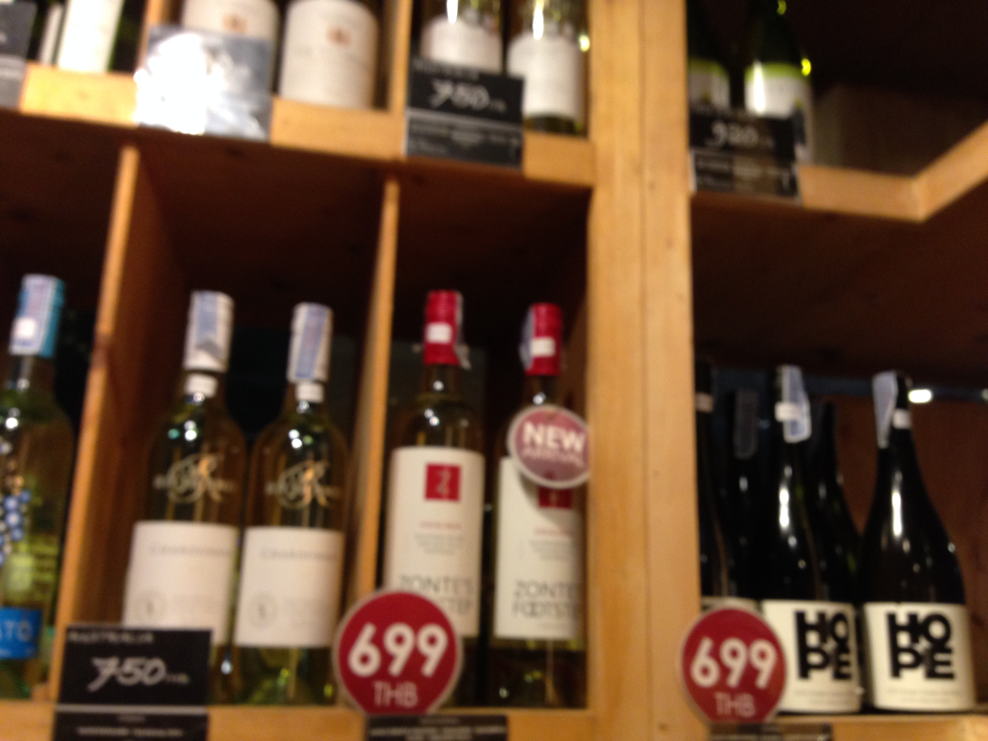 White wine bottles placed in wooden cubby holes in the Wine Connection cellar. Red and black price tags.