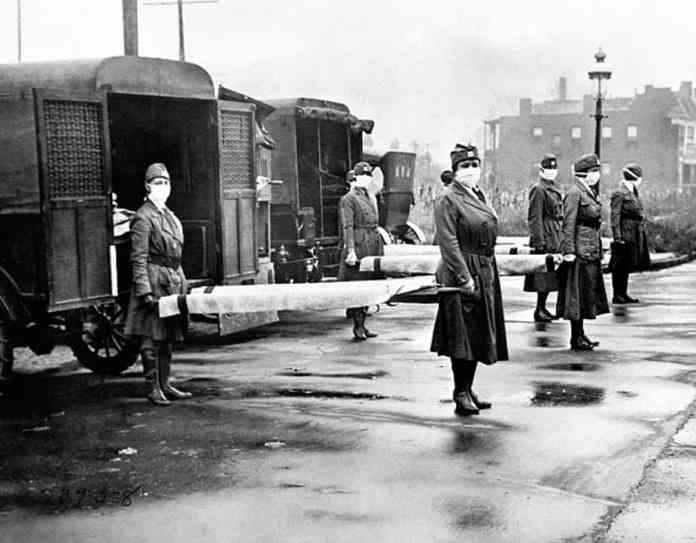 The St Louis Red Cross Motor Corps on duty with mask-wearing women holding stretchers at the backs of ambulances during the global flu epidemic, St Louis, Missouri, October 1918.