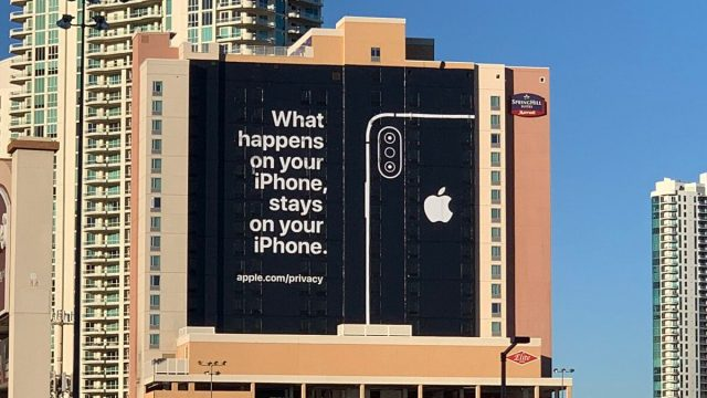 """A billboard on a building. The billboard has a black background with white text that says """"What happens on your iPhone, stays on your iPhone. apple.com/privacy"""" and has an outline of an iPhone next to the text."""