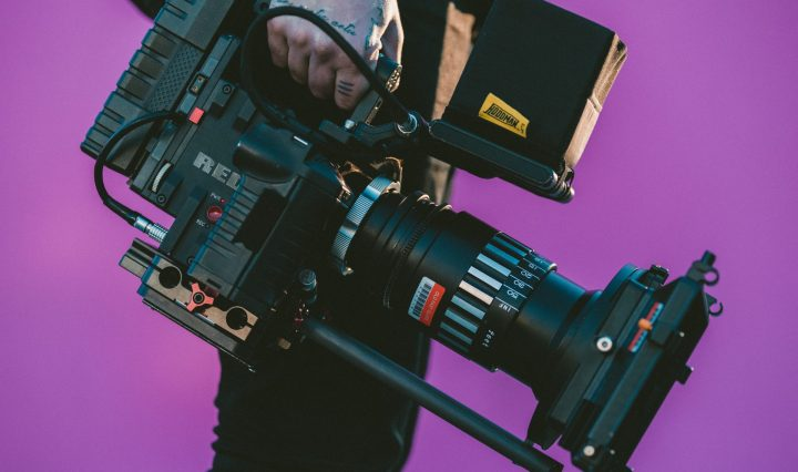 a man holding a camera against the purple background making video for a youtube