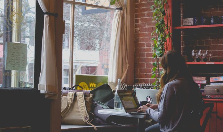 a person sitting in a cafe working on a laptop with adobe spark