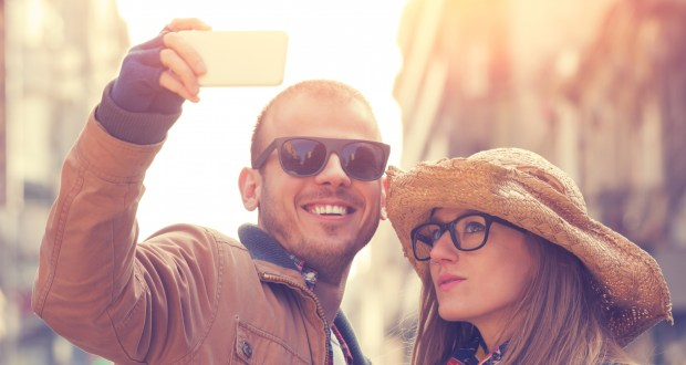 Attractive couple doing selfie outdoors.