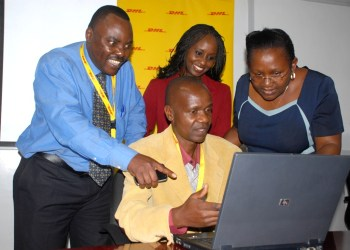 (Seated) Mr. Peter Kuya showcasing the computer to Mr. Kenneth Kaunda HR DHL Express, Eva Ntalani Program Manager Zawadi Africa Education Fund- Kenya     and Mrs. Anne Kyoya Executive Director Zawadi Educational fund