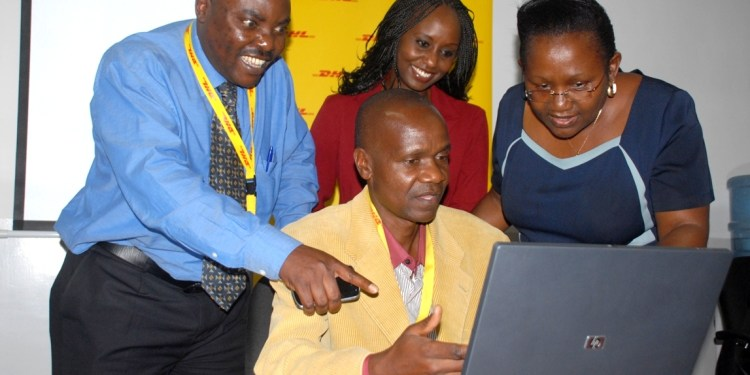 (Seated) Mr. Peter Kuya showcasing the computer to Mr. Kenneth Kaunda HR DHL Express, Eva Ntalani Program Manager Zawadi Africa Education Fund- Kenya     and Mrs. Anne Kyoya Executive Director Zawadi Educational fund