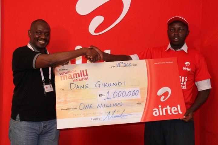 Airtel Kenya IT Director Tony Theuri Presenting a Kshs1 Million cheque to one of the winners Dane Gikundi.