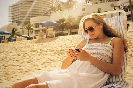 woman-on-beach-using-mobile-phone-on-holiday