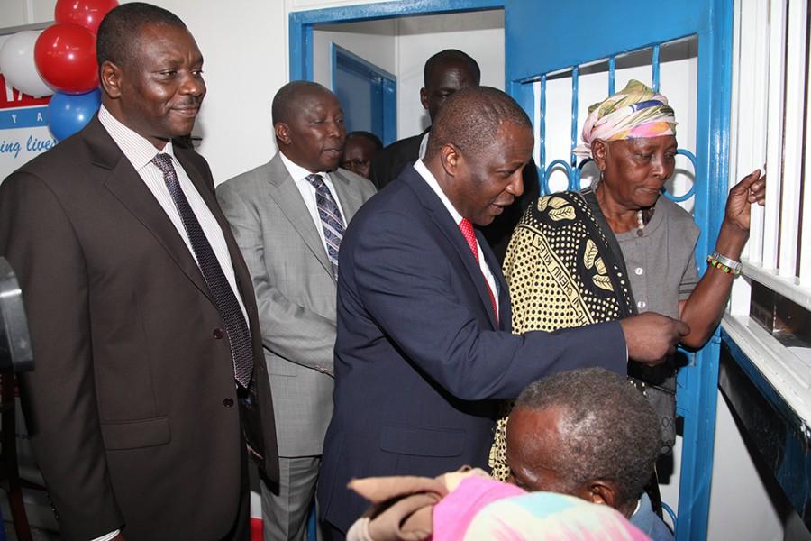 L-R, Dr. Enock Kinaya (postmaster General), Maina Kamanda (MP Starehe), Kazungu Kambi (CS Labour) & katike Mwele (beneficiary).