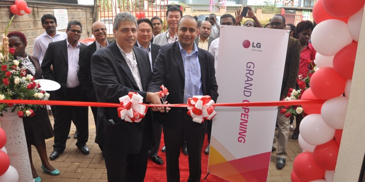 Moses Marji, the LG East Africa Marketing General Manager (left) and Rakesh Singh, the Polestar Kenya General Manager cut a ribbon to mark their distributorship agreement as well as the opening of a new Polestar brand shop in Westlands as staff of the two companies look on