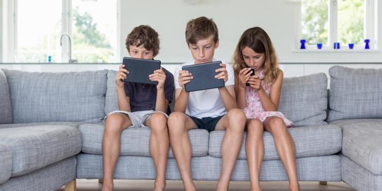 Brothers and sister on sofa with digital tablets and mobile