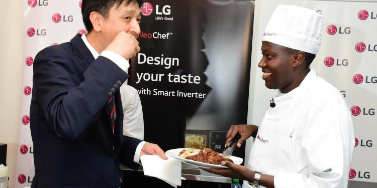 LG Electronics' East Africa Product Manager-Home Appliances Mr. Hangsuk Song is assisted by Chef Raphael to sample a piece of chicken grilled using the company's latest efficient, versatile cooking and energy saving microwave dubbed NeoChef.
