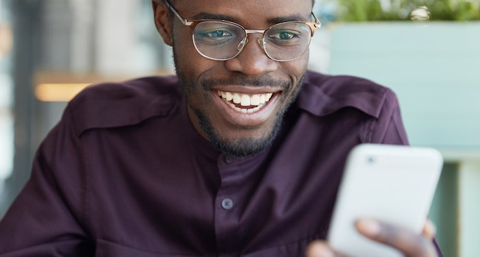Cheerful young businessman in round spectacles and formal wear, checks newsfeed on modern smart phone, connected to wireless internet, has happy look as recieves positive news from colleagues