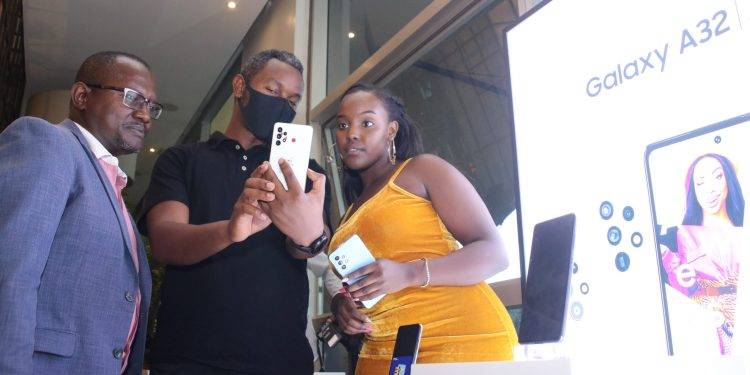 Samsung trainer Nebert Njoka (C) showcases the newly launched Samsung A72 to Samsung Kenya Head of Integrated Mobile Mr. Charles Kimari (L) and Samsung Brand Ambassador Nikita Kering (R) during the Samsung A Series launch at the Urban Eatery in Nairobi Kenya on the 17th of March 2021