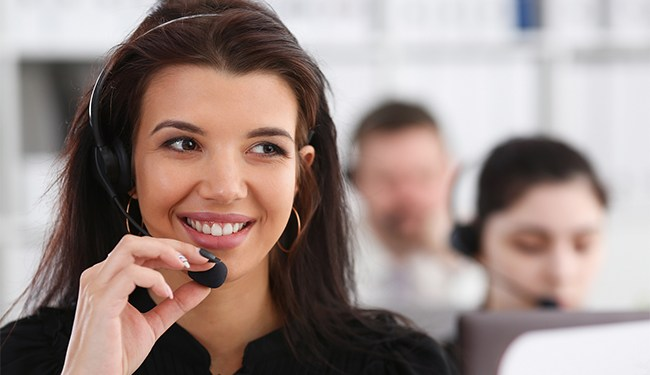Three call centre service operators at work. Portrait of smiling pretty brunette woman at workplace employment effective mediation negotiation participation solve problem real time aid job concept