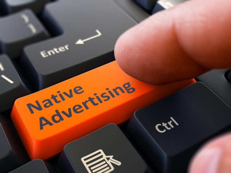 Native Advertising Button. Male Finger Clicks on Orange Button on Black Keyboard. Closeup View. Blurred Background.