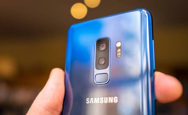 Edinburgh, UK - Close-up of the back of a coral blue coloured Samsung Galaxy S9+ smartphone, showing the dual camera lenses. The phone's variable aperature lens technology is a key new feature of the model.