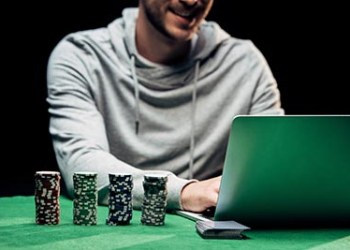cropped view of happy man using laptop near poker chips isolated on black