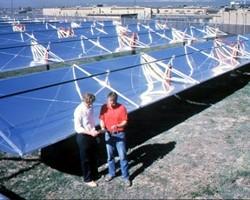 Technicians in front solar panel array (NREL)
