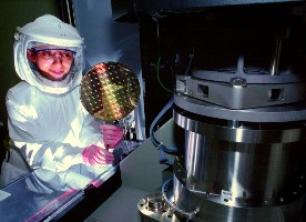 Technician holding a wafer of semiconductor chips (Sandia National Lab)