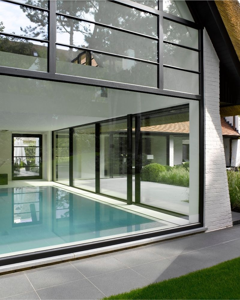 a large steel framed glass wall in swimming pool