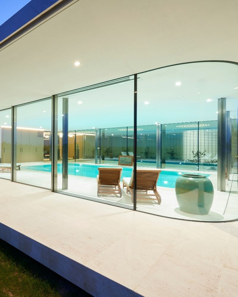 indoor pool with frameless glass walls around it