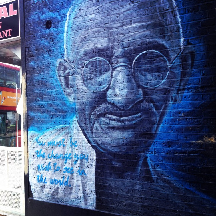 Picture of Ghandi painter on a wall with be the change quote
