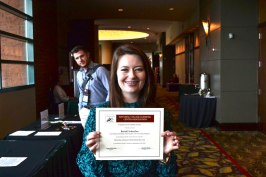 Brandi holding her National College Learning Center Association Certificate